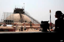 A Nepalese woman looks at the reconstruction work at the Boudhanath Stupa which was damaged in last year's earthquake in Kathmandu, Nepal, Monday, April 25, 2016.