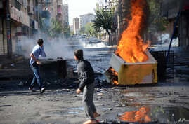FILE - Youths set fire to barricades within sight of Turkish army tanks stationed in Diyarbakir, hours after violent protests by Kurds over the Islamic State group's advance on Kobani, Syria, Oct. 8, 2014.