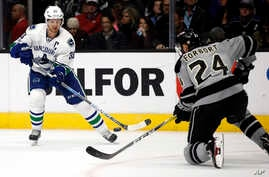 FILE - Vancouver Canucks center Henrik Sedin, left, of Sweden, passes the puck against Los Angeles Kings defenseman Derek Forbort during the first period of an NHL hockey game in Los Angeles, March 4, 2017. The NHL will play its first games in China
