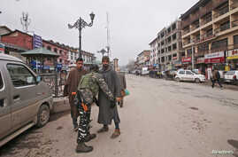 An Indian Central Reserve Police Force (CRPF) personnel frisks a man at a street in Srinagar, Feb. 18, 2019.