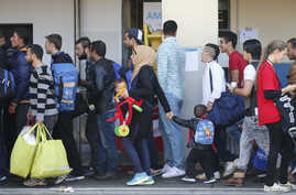 Migrants line up after arriving at a train station in Vienna, Sept. 12, 2015.