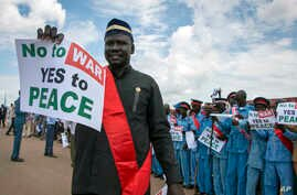 FILE - South Sudanese people hold signs as they await the arrival back in the country of South Sudan's President Salva Kiir, at the airport in Juba, South Sudan, June 22, 2018.