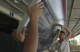FILE - Employees examine newly-made solar panels before boxing for shipment at a factory of Yingli Solar in Baoding, Hebei province, August 2, 2012.