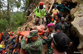 Rescue workers carry a miner who survived the collapse of an illegal gold mine at Bolaang Mongondow regency in North Sulawesi, Indonesia, Feb. 28, 2019.