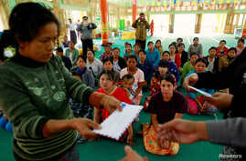 Police give aid to people fleeing from Laukkai, the capital of Kokang in Shan State, who arrived at a monastery functioning as a refugee camp in Lashio, Feb. 16, 2015.