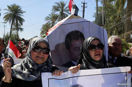 FILE - Iraqi journalists carry a mock coffin at a symbolic funeral for Mohammed Badawi, the Baghdad bureau chief of Radio Free Iraq, in Baghdad's Jadriyah district, March 23, 2014.