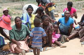 Some women and their children in Mutare West wait for food being cooked in December 2015 under FAO's Livelihoods and Food Security Program in Zimbabwe.