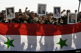 A handout picture released by the official Syrian Arab News Agency (SANA) shows soldiers from the Syrian government forces holding the Syrian flag and pictures of President Bashar al-Assad and his late father Hafez al-Assad, August 1, 2012.