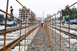 FILE -A laborer works at a light railway transit system under construction in Ethiopia's capital, Addis Ababa, June 25, 2014. Profitability concerns have slowed funding from China for some rail projects.