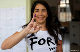 A woman shows her ink-stained finger after casting her vote during the parliamentary election in Beirut, Lebanon, May 6, 2018.