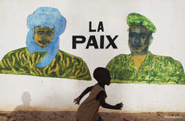 """A boy runs in front of a mural that reads """"Peace"""", in Timbuktu, July 24, 2013."""