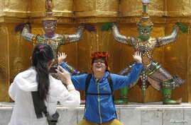 FILE - A Chinese tourist strikes a similar pose to statues as they visit the Grand Palace in Bangkok, March 23, 2015.