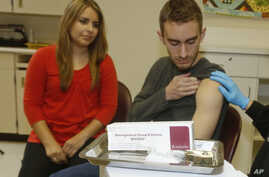 FILE - Meningococcal meningitis survivor and vaccination advocate Leslie Meigs looks on as her brother Andrew (18), a college student in Texas, receives Bexsero(R), a meningococcal group B vaccine approved by the FDA for ages 10-25. Feb. 24, 2015.