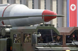 FILE - North Korean soldiers salute in a military vehicle carrying a missile during a parade to commemorate the 60th anniversary of the signing of a truce in the 1950-1953 Korean War, at Kim Il-sung Square in Pyongyang, July 27, 2013.