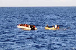 File - An Italian Navy photo taken on Dec. 4, 2014, shows a rescue crew on a dinghy (R) approaching migrants on a boat some 40 miles (65 kilometers) from the Libyan capital, Tripoli.