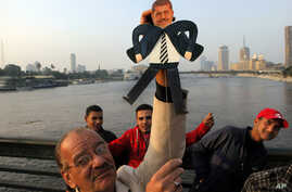 Standing on the Qasr El-Nile Bridge in Cairo during a February 10 anti-Muslim Brotherhood protest, artist Mohammed Darwish displays a puppet he designed of Egypt's former president, Mohammed Morsi.