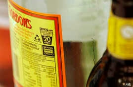 FILE - A small label with a health warning is displayed on an alcohol bottle in Sydney, Australia,
