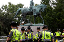 Virginia state troopers stand under a statue of Robert E. Lee before a white supremacists rally in Charlottesville, Va., Aug. 12, 2017.