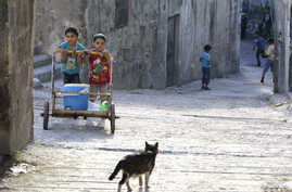 Children push a cart carrying water in the Al-Bayada neighborhood of Aleppo on April 26, 2014.