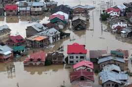 Flood-affected people row boats past partially submerged buildings in floodwaters in Srinagar, India,