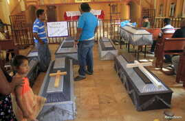 FILE - Relatives stand next to the coffins of seven of 13 vigilantes — all killed in a clash between armed vigilante groups just north of Acapulco — before a funeral mass in the town of Xolapa, Mexico, June 7, 2015.