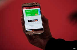 FILE - A woman uses her smartphone for a MasterCard-develped cashless transaction.