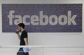 FILE - Facebook employee walks past a sign at company headquarters in Menlo Park, California.