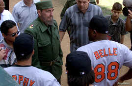 A March 28, 1999 file photo shows then-Cuban President Fidel Castro talking with Baltimore Orioles slugger Albert Belle (88) prior to the exhibition game between the Orioles and a Cuban National Team