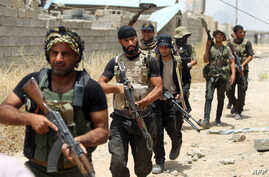 Iraqi Shi'ite fighters from the Popular Mobilization units deploy in the city of Baiji, north of Tikrit, as they fight alongside Iraqi forces against the Islamic State jihadist group to try to retake the strategic town for a second time, June 9, 2015