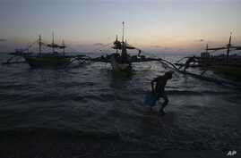 In this May 7, 2013 photo, a Filipino boy carries a container from newly arriving fishing boats as the sun sets in the coastal town of Infanta, Pangasinan province, northwestern Philippines. Since China took control of the Scarborough Shoal last year