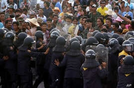 In this photo taken on Sept. 5, 2013, rubber farmers confront and scuffle with Thai anti-riot police officers on a highway in Prachuab Khirikhan province, southern Thailand.