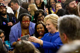 Democratic presidential candidate Hillary Clinton takes pictures with supporters after a campaign event at the Central Baptist Church in Columbia, South Carolina, Feb. 23, 2016.