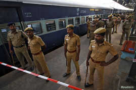 Indian policemen stand guard next to a passenger train in which two explosions occurred, at the railway station in the southern Indian city of Chennai, May 1, 2014.