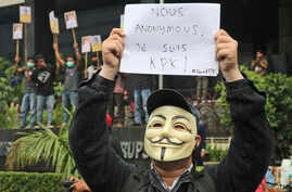 "FILE - A masked supporter of Indonesian Corruption Eradication Commission (KPK) holds up a poster that reads ""I am KPK"" during a protest against the arrest of the deputy head of the Corruption Eradication Commission Bambang Widjojanto by the police,"