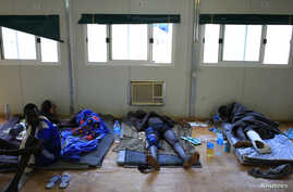 Displaced men recuperate from their injuries as they rest on the floor at a United Nations hospital in Tomping camp, near Juba, Jan. 7, 2014.