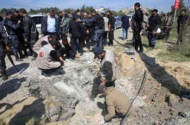 Hamas security services personnel inspect the site of a Tuesday explosion that occurred as the convoy of Palestinian Prime Minister Rami Hamdallah entered Gaza through the Erez crossing with Israel, on the main road in Beit Hanoun, Gaza Strip,, March