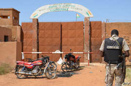 A Nigerien gendarme stands near calcined motorcycles used by assailants, in front of the the prison of Koutoukale, near Niamey, following an attack on Oct. 17, 2016.