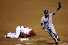 Boston Red Sox first baseman Mike Napoli celebrates after tagging out St. Louis Cardinals' Kolten Wong on a pick-off attempt to end Game 4 of baseball's World Series, Oct. 27, 2013.