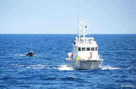 A Japanese coast guard patrol vessel tows a boat carrying nine people off the coast of Noto Peninsula, in northwestern Japan, Sept. 13, 2011. On Thursday, Japan returned to North Korea three crew members from a capsized fishing boat off the Noto Peni