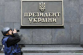 "A photographer takes a picture of a sign reading ""President of Ukraine"" at the entrance to the presidential administration building in Kyiv Feb. 22, 2014."