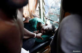 An injured man who medics say was shot by live fire during a protest of supporters of Kenyan opposition leader Raila Odinga is treated in a clinic in Kisumu, Kenya, Oct. 25, 2017.