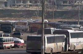 In this still image taken from video from Syria TV vehicles wait to cross into east Aleppo at Ramouseh crossing point, Sunday, Dec. 18, 2016. Dozens of vehicles were on standby at the Ramouseh crossing point near Aleppo on Sunday morning.