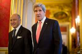 U.S. Secretary of State John Kerry, right, walks to a meeting with France's Foreign Minister Laurent Fabius at the Quai d' Orsay in Paris, March 27, 2013.