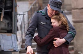 """This image released by 20th Century Fox, April 9, 2013, shows Geoffrey Rush, left, and Sophie Nélisse in a scene from """"The Book Thief,"""" about a girl who loves books."""