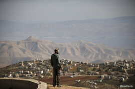 Jewish settler Refael Morris stands at an observation point overlooking the West Bank village of Duma, near Yishuv Hadaat, an unauthorized Jewish settler outpost January 5, 2016.