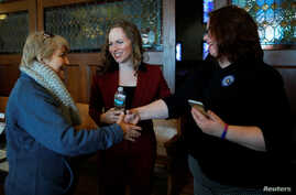 FILE - Democratic candidate for the U.S. Congress Alexandra Chandler, center, a transgender, former Naval Intelligence analyst, introduces her wife Cathy, right, to a voter in Haverhill, Massachusetts, Jan. 27, 2018.