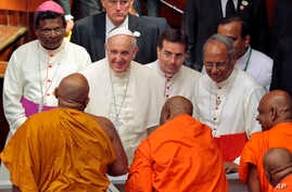 Pope Francis smiles as he speaks to Buddhist monks after an inter-religious meeting in Colombo, Sri Lanka, Tuesday, Jan. 13, 2015.