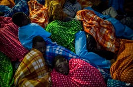 Refugees and migrants rest aboard the Golfo Azurro, a Spanish rescue ship, after being found off the Libyan coast, early in the morning on Feb. 23, 2017.