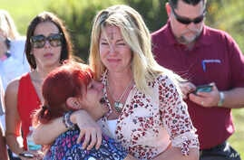 Parents wait for news after a reports of a shooting at Marjory Stoneman Douglas High School in Parkland, Fla., on Feb. 14, 2018.