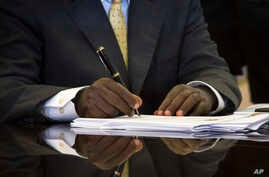Uganda's President Yoweri Museveni signs a new anti-gay bill that sets harsh penalties for homosexual sex, in Entebbe, Uganda, Feb. 24, 2014.